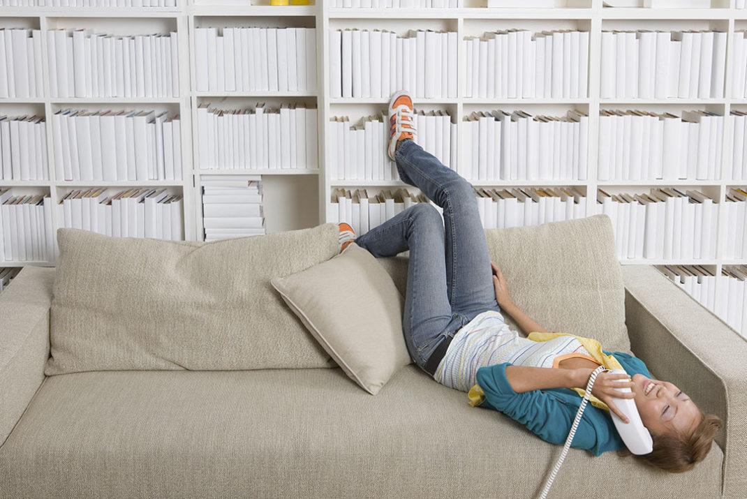 Immagine di donna distesa sul divano che sta telefonando.