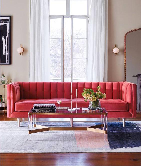 Divano rosso fragola su soggirono moderno con tappeto in toni del grigio e rosa.