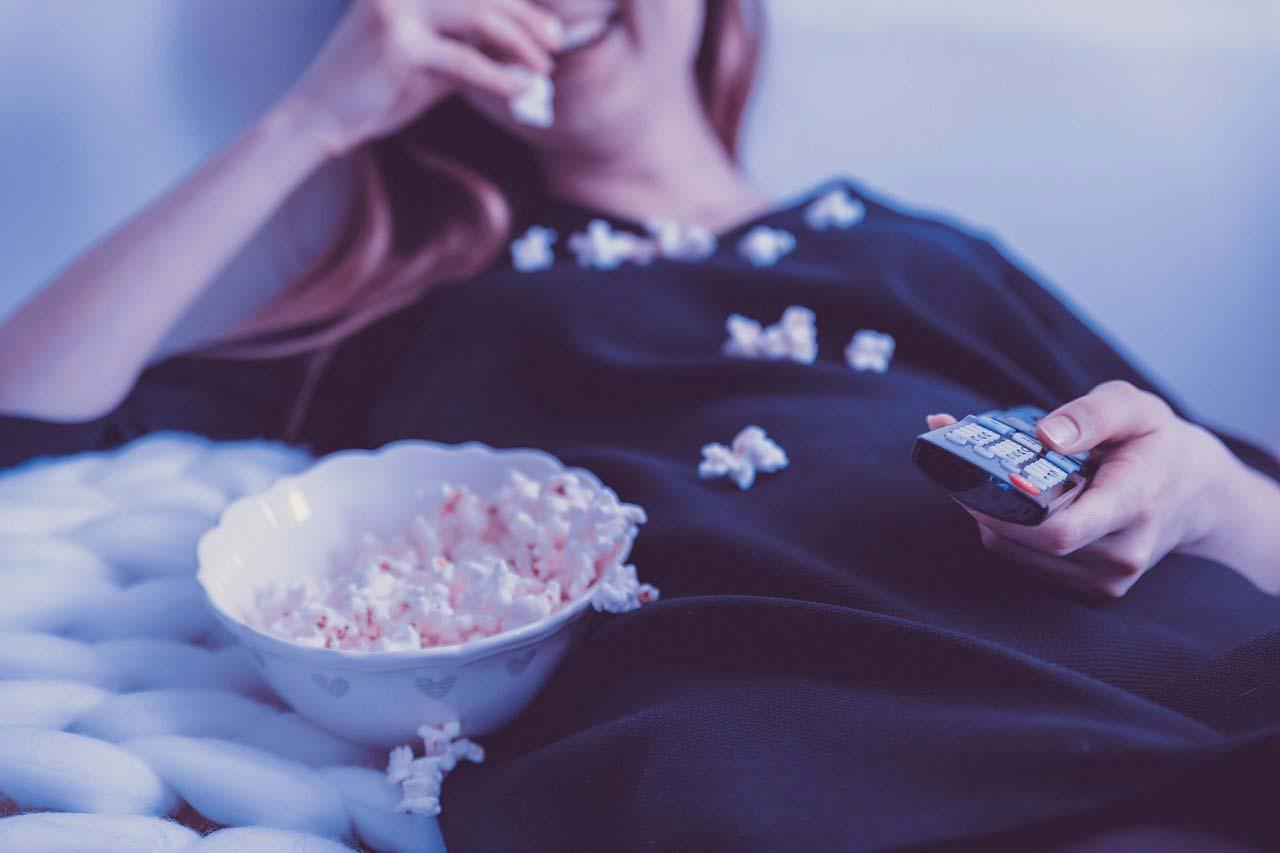 donna che guarda la tv mangiando pop corn