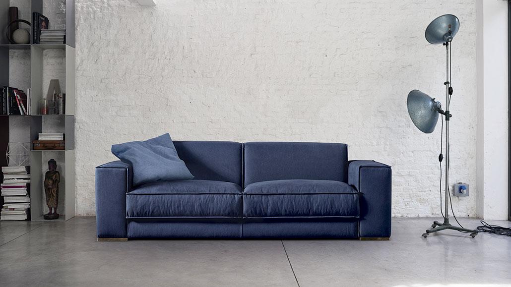Divano con seduta in misto piuma a 3 posti. Un divano morbido rivestito di tessuto in colore blu.
