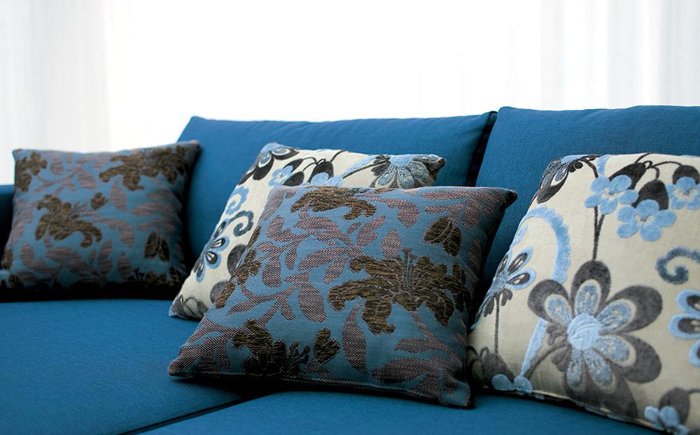 Divano Blu con cuscini in fantasia floerale classici.