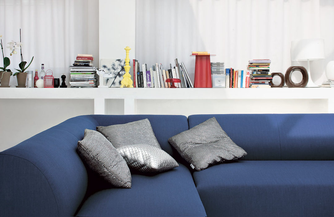 Schienale di divano blu con cuscini in fantasia colore argento.