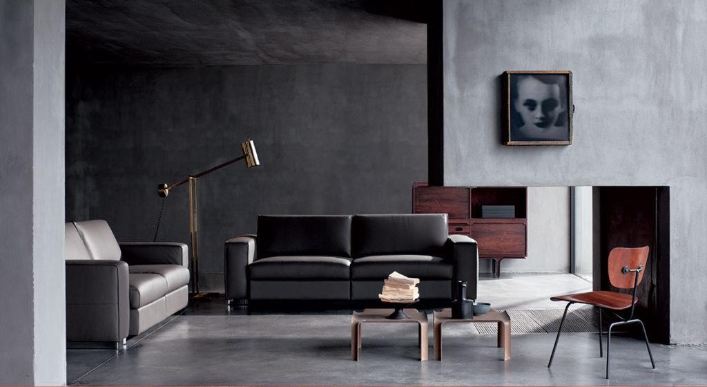 Salotto elegante con divano in pelle scura.