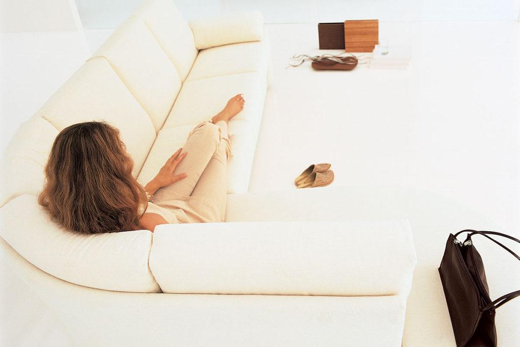 donna seduta divano gambe alzate.
