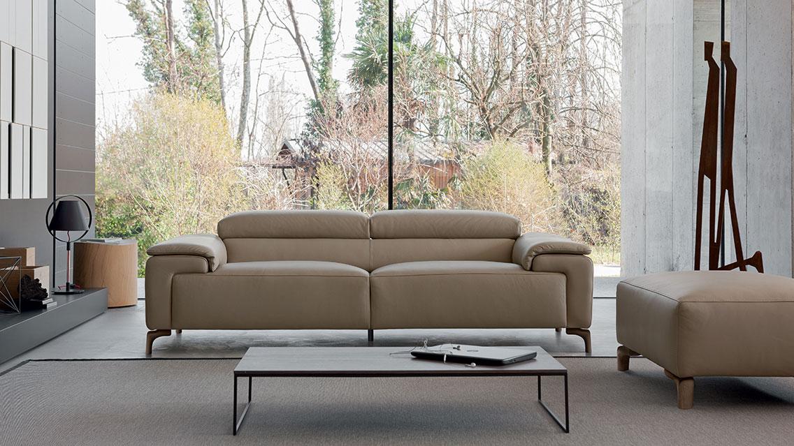 divano con schienale basso e pouf piccolo in pelle beige grigio.